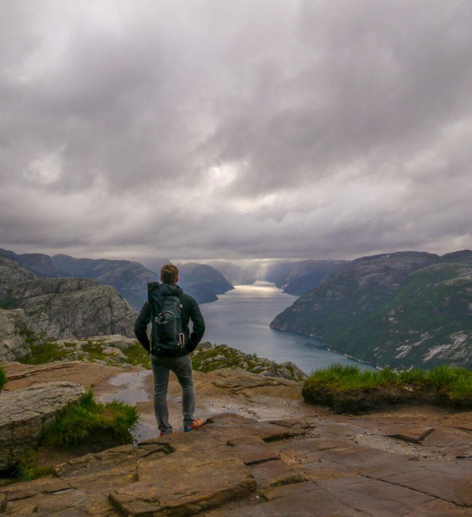 fjord norway water men rock mountain sun