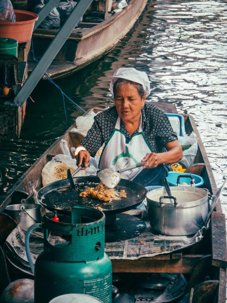 thailand taling-chan schwimmender-markt bangkok frau boot essen