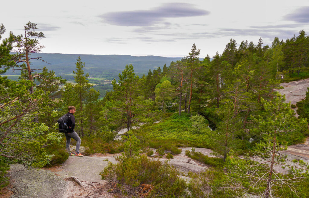 norway hiking man tree stone sky clouds