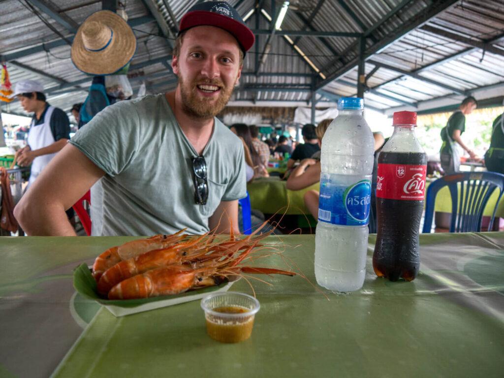 thailand taling-chan schwimmender-markt bangkok mann essen