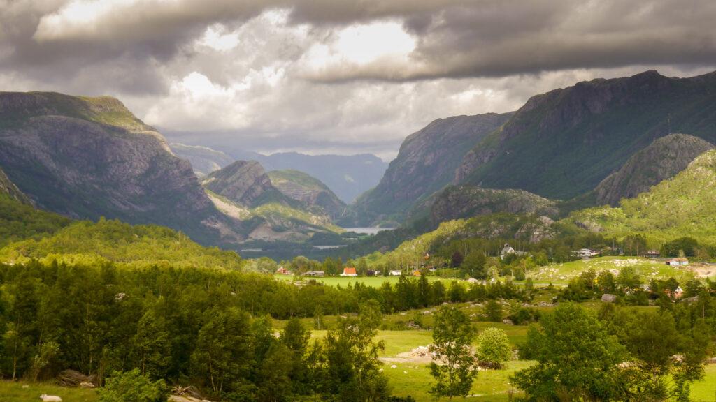 norway fjord water rock mountain tree sun green