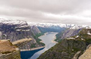 norwegen berg trolltunga frau see wolken schnee