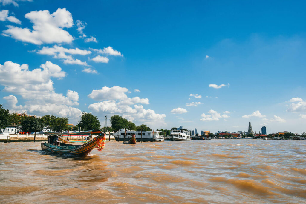 thailand bangkok city river people boat sky clouds temple