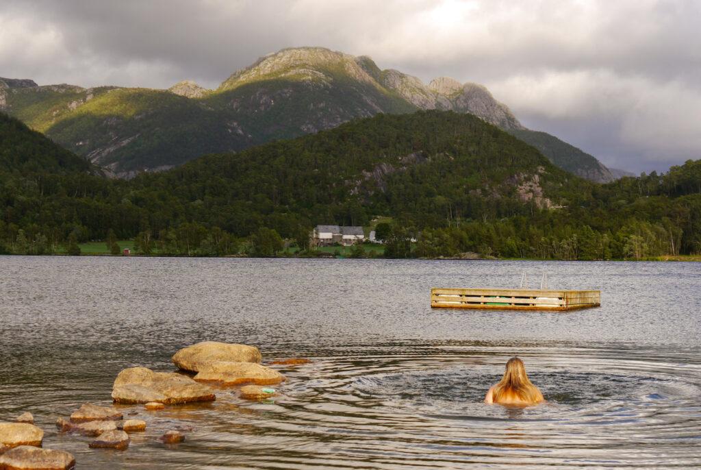 norwegen preikestolen fjord bäume wasser berg felsen see frau