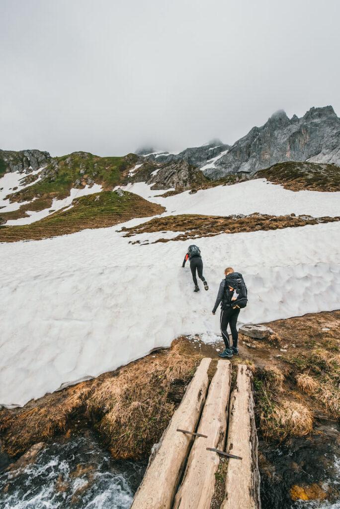 vorarlberg rätikon hiking clouds bridge snow mountains woman lünersee brandnertal