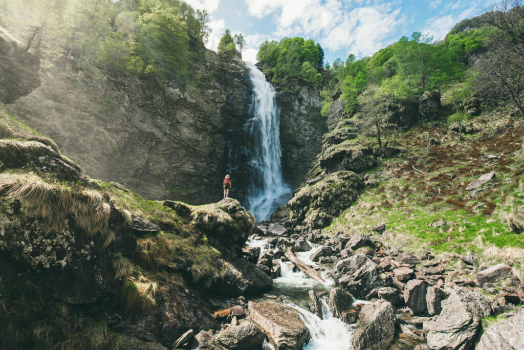 schweiz tessin verzasca-tal cascata-la-froda sonogno wasserfall frau wandern wasser